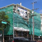 A perfect example of a space's potential to hold art. Green drops protect sacaffolding and a paint crew's work. They left the billboard open, with neglected, rotting ads on it. Easy access for a nimble artist, or someone who wants to take it down!